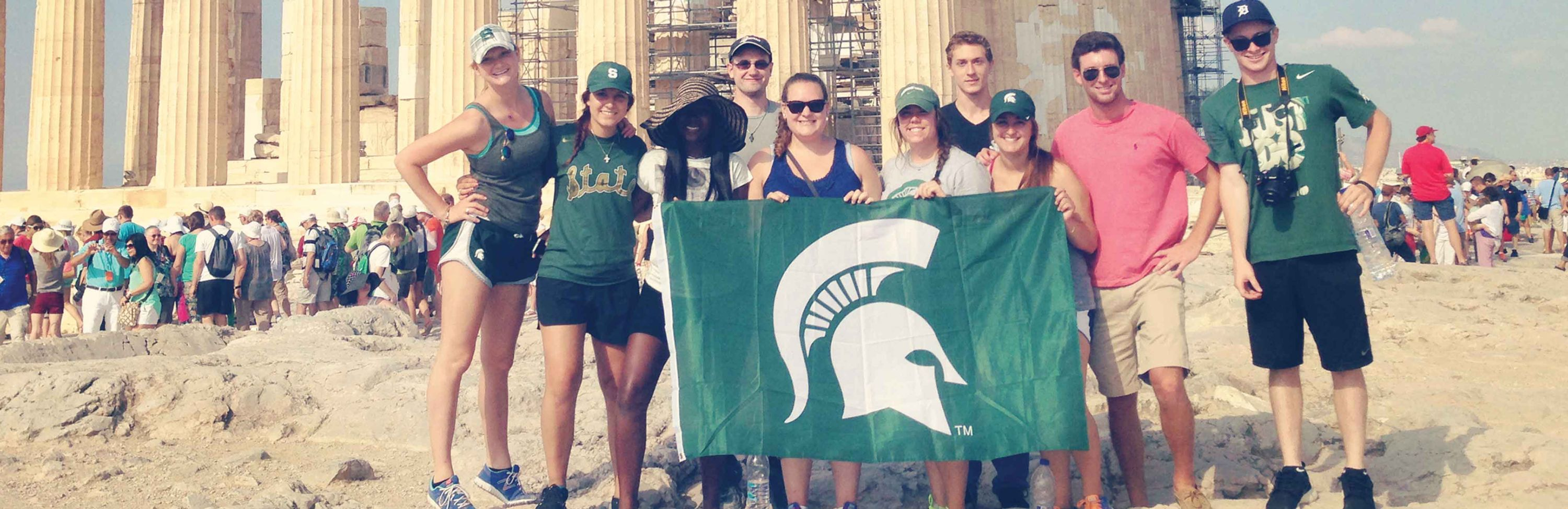 students holding an MSU flag